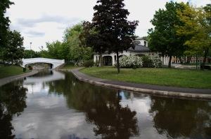 Un étang, un chalet sur une île, un moulin à eau. Et tout à côté, un établiseement scolaire