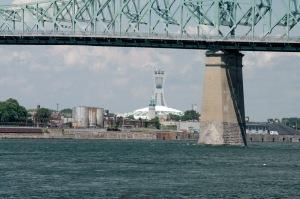 C'est un départ. Au premier plan, le pont Jacques-Cartier derrière lequel le stade olympique semble surveiller l'activité portuaire