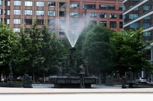 La sculpture-fontaine « La Joute » est mise en valeur dans un bassin circulaire dans le Quartier international de Montréal